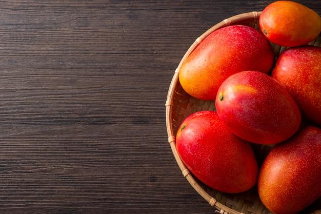 Frutto di mango fresco e bello in un cesto di bambù su uno sfondo di legno scuro, copia spazio (spazio testo), vuoto per il testo, vista dall'alto.