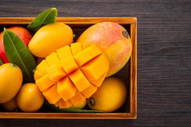 Fresco e bellissimo frutto di mango impostato in una scatola di legno con fette di mango a dadini pezzi su un legno scuro dello sfondo, copia spazio (spazio testo), vuoto per il testo