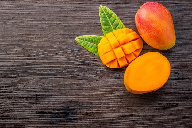 Frutto di mango fresco e bello con pezzi di mango tagliati a dadini su uno sfondo di legno scuro, copia spazio (spazio testo), vuoto per testo, vista dall'alto.