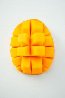 Frutto di mango fresco e bello con pezzi di mango a dadini affettati su uno sfondo azzurro, copia spazio (spazio testo), vuoto per testo, vista dall'alto.
