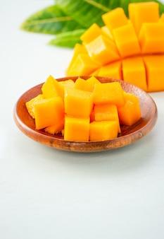Frutto di mango fresco e bello con pezzi di mango tagliati a dadini su uno sfondo azzurro, copia spazio (spazio testo), vuoto per il testo.