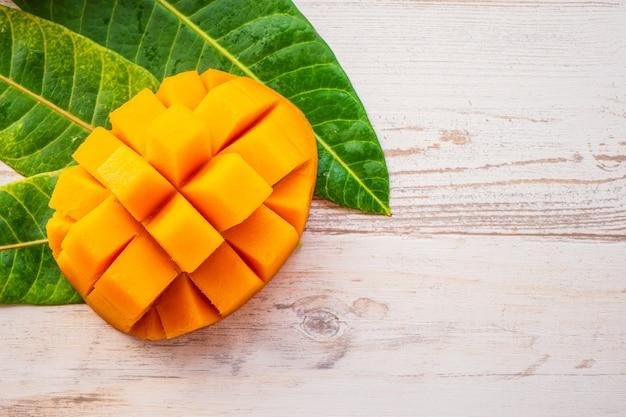 Frutto di mango fresco e bello con pezzi di mango tagliati a dadini su uno sfondo di legno chiaro, copia spazio (spazio testo), vuoto per testo, vista dall'alto.