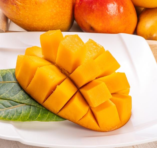 Mango fresco e bello in una piastra bianca con pezzi di mango tagliati a dadini isolati con fondo in legno chiaro, spazio copia (spazio testo), vuoto per il testo