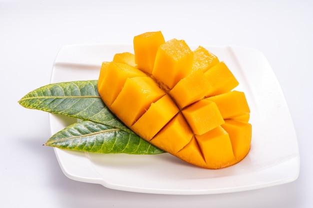 Mango fresco e bello in una piastra bianca con fette di mango a cubetti isolati con sfondo bianco, copia spazio (spazio testo), vuoto per il testo