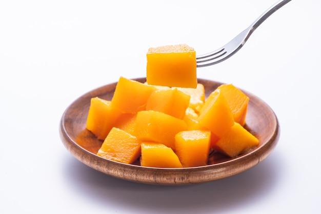 Mango fresco e bello in un piatto di legno con pezzi di mango tagliati a dadini isolati con sfondo bianco, spazio copia (spazio testo), vuoto per il testo