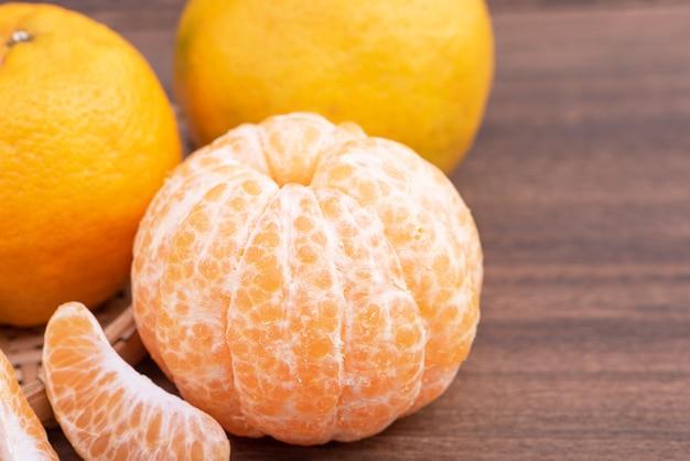 Mandarino fresco e bello di colore arancione sul setaccio di bambù sopra la tavola di legno scuro. frutta stagionale e tradizionale del nuovo anno lunare cinese, fine su.