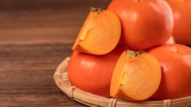 Kaki cachi dolce affettato bella fresca sulla tavola di legno scuro con priorità bassa del muro di mattoni rossi, concetto di design di frutta cinese nuovo anno lunare, primi piani