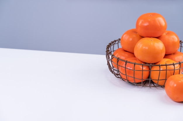 Kaki cachi dolce a fette bella fresca isolato sul tavolo da cucina bianco con sfondo blu grigio, concetto di design del nuovo anno lunare cinese, primi piani.
