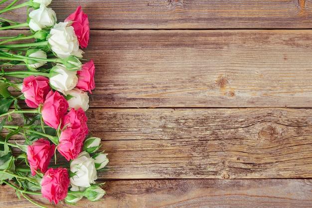 Belle rose bianche e rosa fresche su vecchio fondo strutturato di legno scuro, vista superiore, spazio della copia. cornice fiori vintage