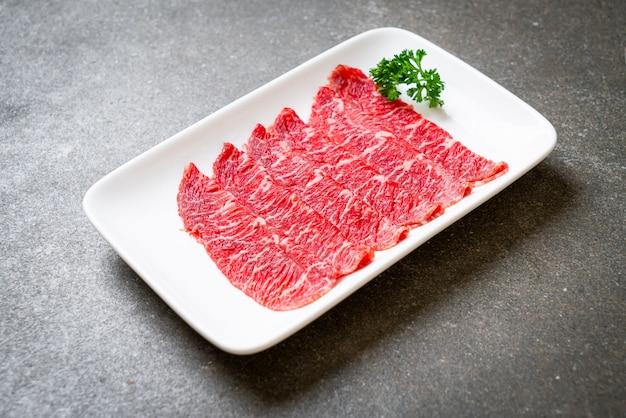 Manzo fresco crudo affettato con consistenza marmorizzata servito per sukiyaki e shabu o yakiniku