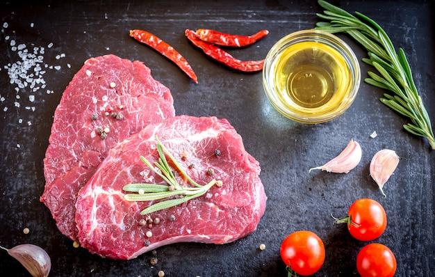 Bistecche di manzo fresche con ingredienti sullo sfondo scuro