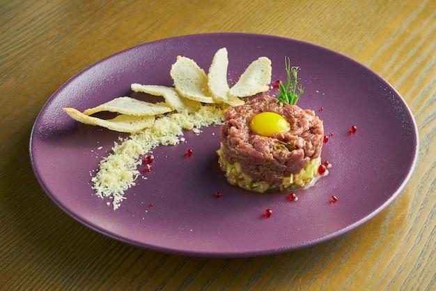 Tartara di manzo fresca con capperi, tuorlo d'uovo segato e parmigiano. antipasto delizioso