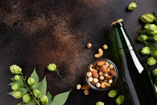 Spuntini freschi della bottiglia di birra e luppoli verdi sul fondo di lerciume