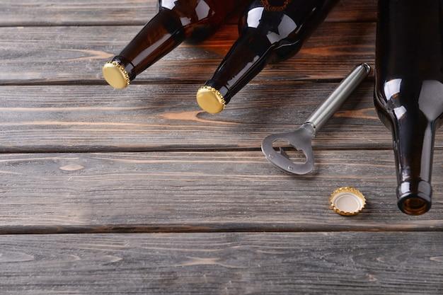 Birra fresca in bottiglie di vetro e apriscatole su fondo in legno