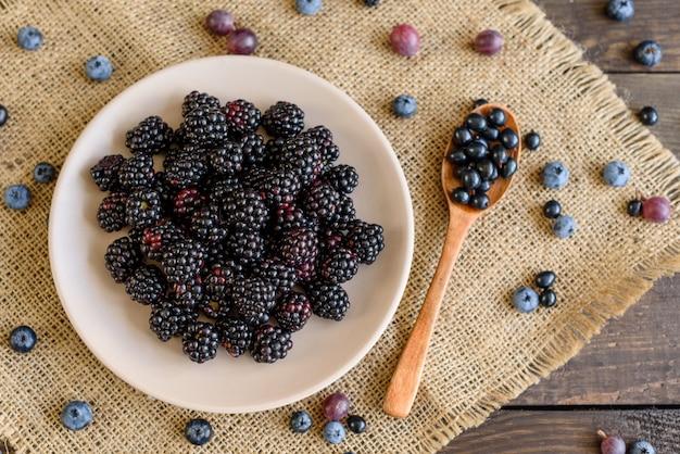 Bacche fresche di mirtillo, mora e uva spina su un piatto