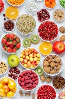 Bacche fresche, frutta, noci su un legno bianco