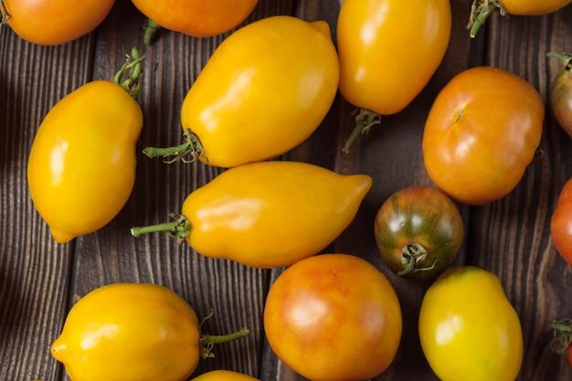 Pomodori freschi grandi e piccoli su fondo di legno scuro