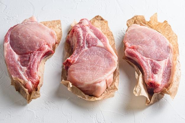 Carne di maiale organica del taglio della bio carne cruda fresca sulla vista laterale di pietra bianca della tavola tre pezzi.