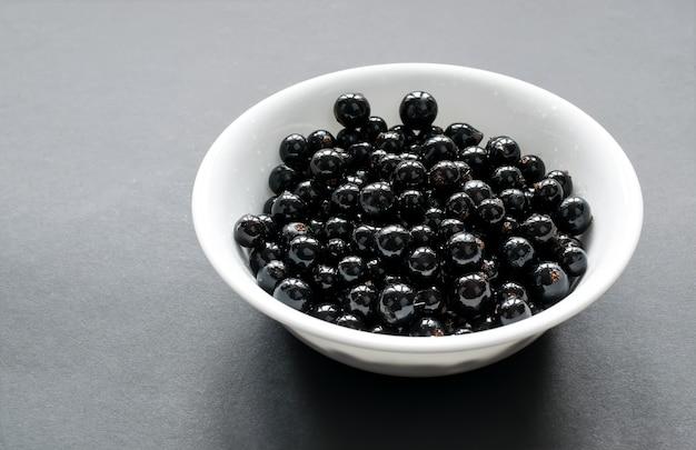 Ribes nero fresco su un piatto bianco come la neve, che si trova su un tavolo nero. vista laterale