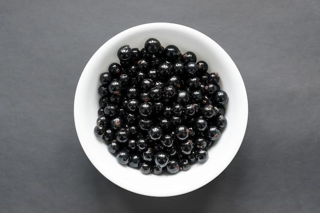 Ribes nero fresco su un piatto bianco come la neve, che si trova su un tavolo nero. vista dall'alto