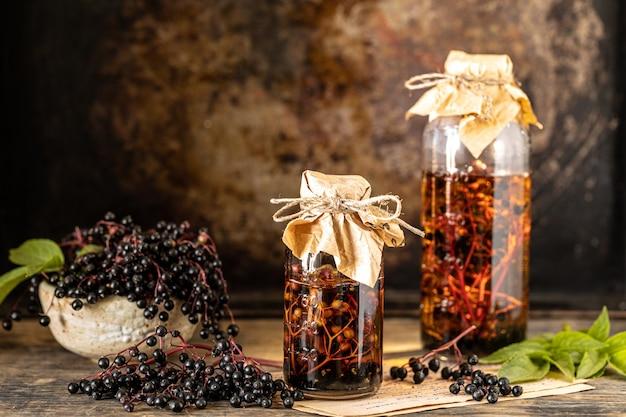 Sciroppo di sambuco nero fresco in una bottiglia di vetro su un tavolo di legno. copia spazio