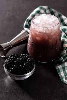Blackberry cocktail fresco in vetro freddo sul nero