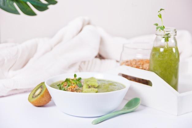 Ciotola di frullato verde mescolata fresca con muesli e semi di chia. concetto di salute e disintossicazione.
