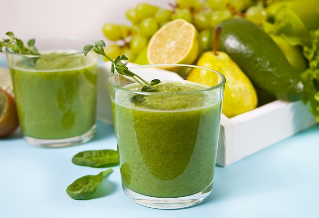 Frullato verde mescolato fresco in bicchieri con frutta e verdura. concetto di salute e disintossicazione.