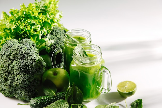 Frullato verde misto fresco in barattolo sulla tavola bianca. detox e concetto di dieta. cibo vegetariano.