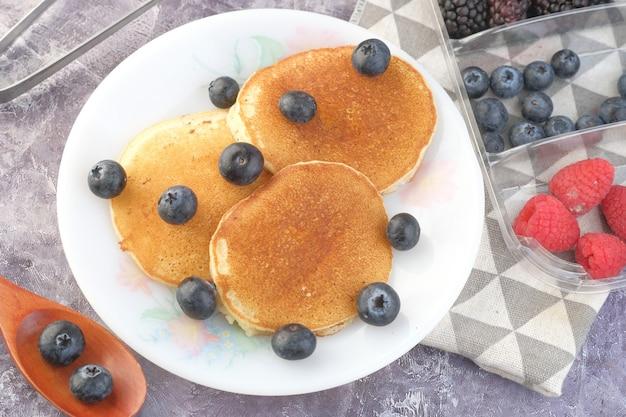 Bacca blu fresca sulla torta della vaschetta sul tavolo
