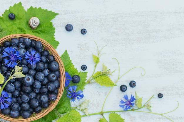 Mirtilli freschi nel cestello con fiori e foglie modello vista dall'alto. cibo sano sul tavolo bianco mock up. bacca deliziosa, dolce, succosa e matura con copia spazio per il testo