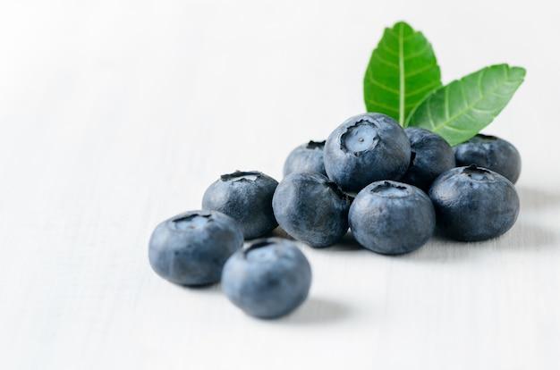 Frutta fresca del mirtillo con la foglia su fondo di legno bianco, concetto sano dei friuts