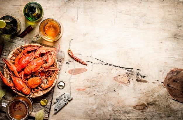 Aragosta bollita fresca con birra sulla tavola di legno.