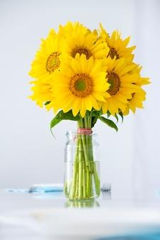 Mazzo fresco dei girasoli della margherita in vaso di vetro sulla tavola bianca fiori estivi all'interno della casa