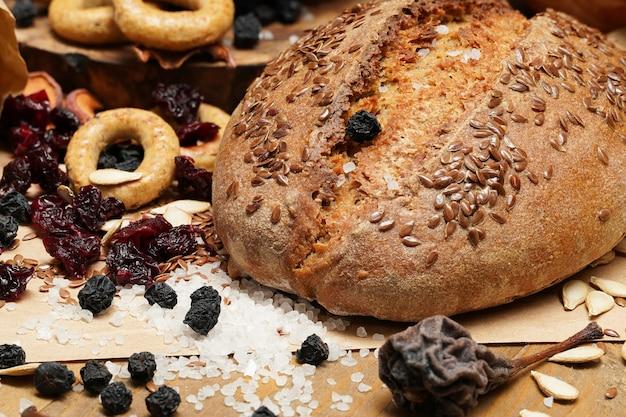Pane fresco, bagel, frutta secca, semi, sale, vaso e grano sul legno - natura morta e concetto di mangiare sano