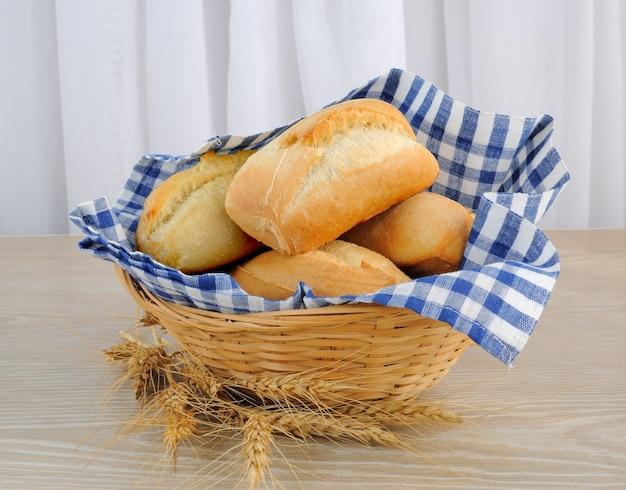 Pane fresco in un cestino con un panno di copertura spighe di grano