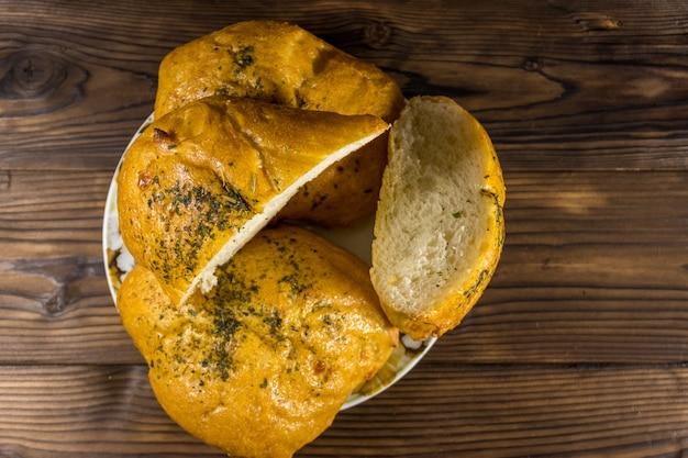 Ciabatta del pane fresco su un piatto sulla tavola di legno. vista dall'alto