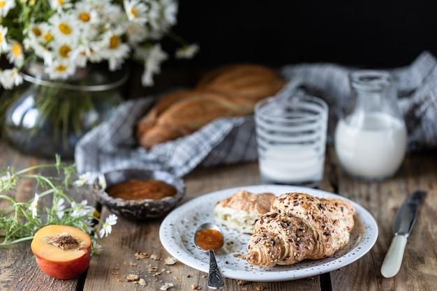 Pane e croissant freschi con inceppamento del latte e della pesca o dell'albicocca su una tavola di legno. bouquet di margherite rustico