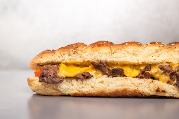Panino di pane fresco con carne e formaggio in un taglio.