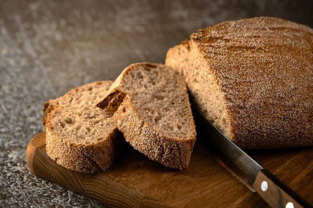 Fetta di pane fresco e coltello da taglio sul tagliere di legno