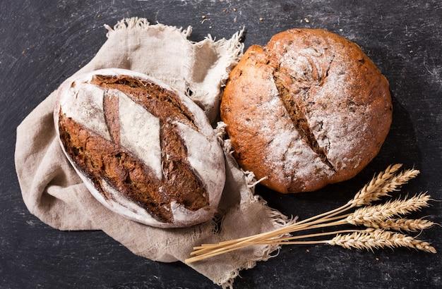 Pane fresco con spighe di grano sul tavolo scuro, vista dall'alto