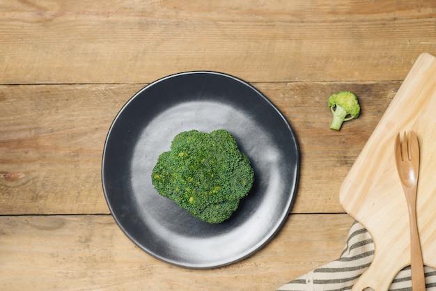 Broccoli freschi in piatto su un fondo di legno