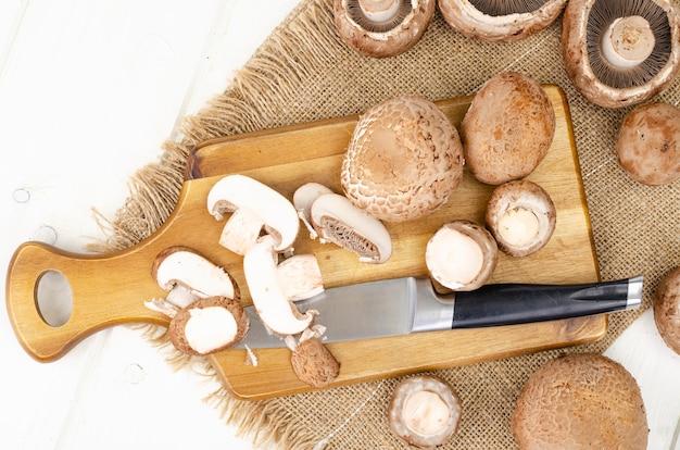 Funghi prataioli coltivati marroni freschi su fondo di legno. foto dello studio.