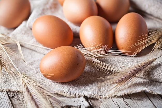 Uova fresche marroni e spighe di grano