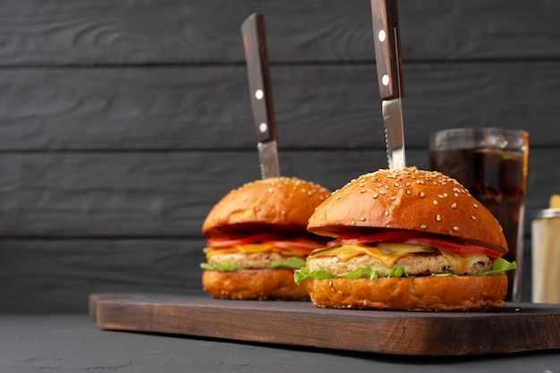 Hamburger e patatine fritte freschi su fondo di legno nero