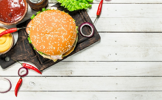 Hamburger fresco di manzo con formaggio e verdure. su uno sfondo di legno bianco.