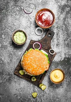 Hamburger fresco di manzo con verdure e salse varie. su fondo rustico.