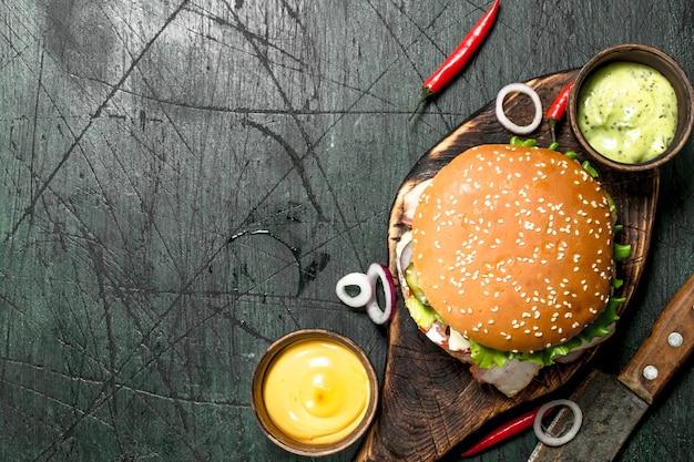 Hamburger fresco con carne di manzo, pancetta e verdure fresche. su fondo rustico.