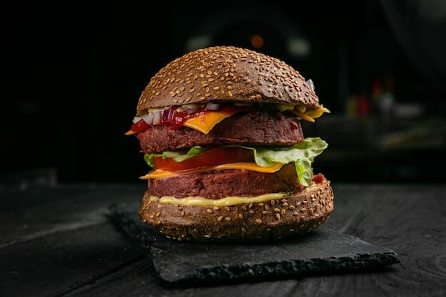 Hamburger fresco con carne e verdure vegane, cosparso di semi di sesamo