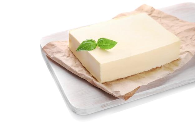 Blocco di burro fresco sul tagliere di legno isolato su bianco
